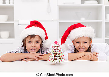 Happy christmas kids with their gingerbread decorated tree