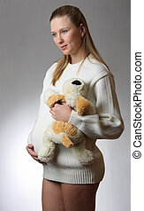 Beautiful pregnant woman with toy
