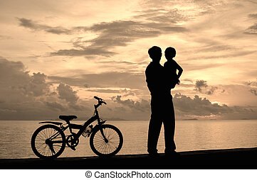 Family - Biker family silhouette  at the beach at sunset.
