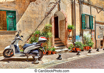 Motorcycle on cobbled street in Ventimiglia, Italy. -...
