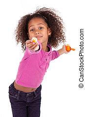 Little African Asian girl sharing a tangerine