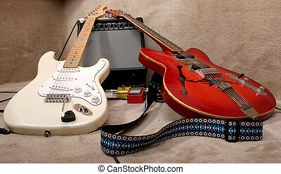 two guitars - the red and cream electric guitars lay on the...