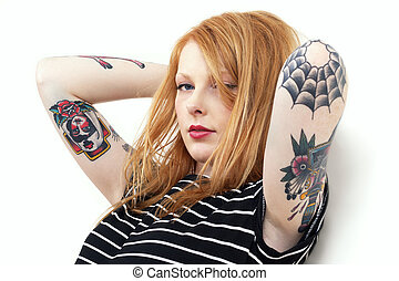 Strawberry blonde with tattooed arms leaning against a white...