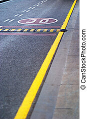 Speed limit sign painted on a road with yellow markings - 30...