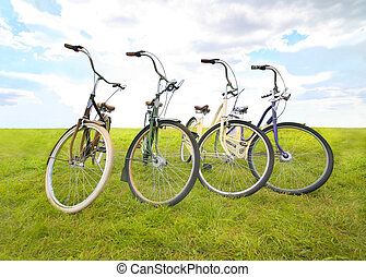 four bicycles on meadow against the sky