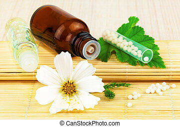 Homeopathic medication with flower and leaf on the mat