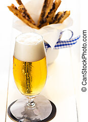 pretzel sticks and beer - A glass of beer and spicy puff...