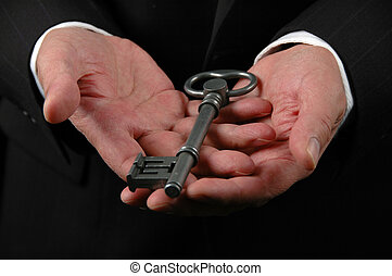Hands Holding Key - Hands holding a large key symbolizing...