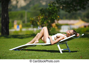 girl sitting in a white lounge on a green grass