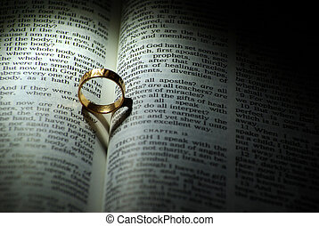 ring - Wedding ring and heart shaped shadow over a Bible