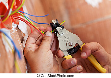 Electrician peeling off wires - Electrician peeling off...