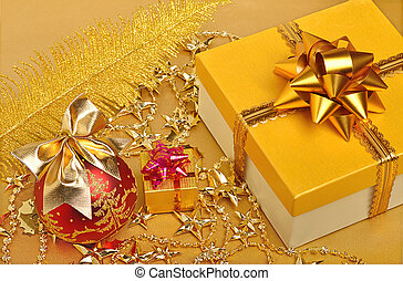 Golden gift boxes, christmas bauble, plume, garland on the...