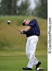 Golf tee shot - a golfer holding his finish after tee shot