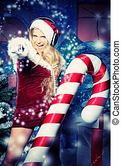 point - Beautiful young woman in Santa Claus clothes and...