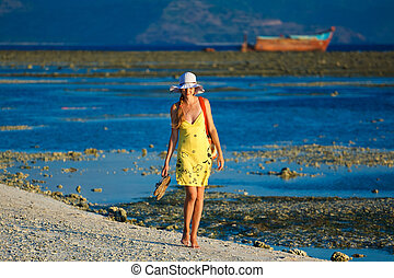 Lonesome woman goes for a walk at sundown on the beach