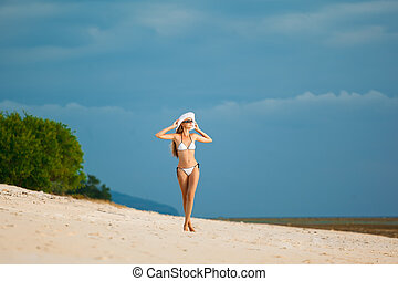 A beautiful woman wearing white bikini on a vacant beach in paradise