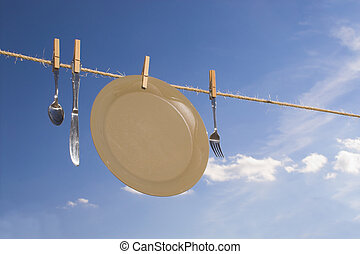 Drying Dishes - Dishes hung out to dry on a clothesline.