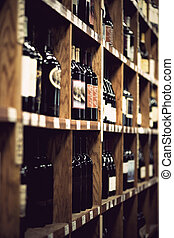 Wine bottles on wooden shelf in wine store. Vintage look.