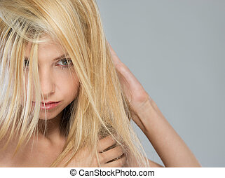 Portrait of blond girl with falling on face hair