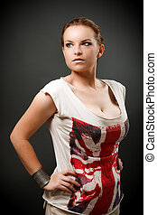 Beautiful redhead woman in studio standing with hand on hip...