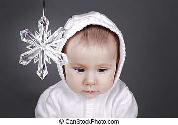 baby with snow flake - beautiful baby girl is sitting sad...