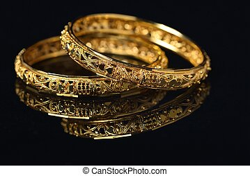 Bangles - Beautiful golden bangles isolated on black...