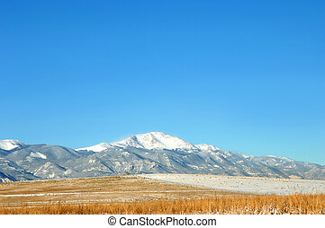 Pikes Peak View - Pikes Peak is covered in snow and field is...