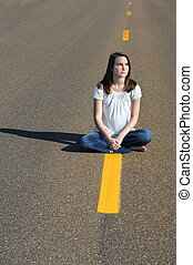 Decision time - Young woman sits straddling the yellow line...