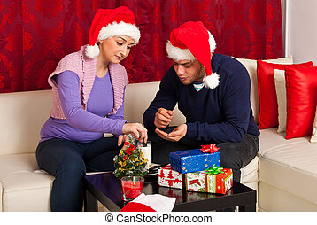 Happy Xmas couple eats biscuits and sitting on sofa in their...