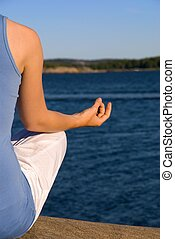cutout of a woman doing yoga at the sea