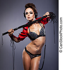 Young sexy woman mistress in headphones and whip in erotic...