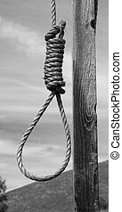 Hangmans Noose next to pole in black and white with hill in...