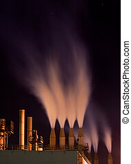 Smokestacks at night - Factory smokestacks spewing smoke...