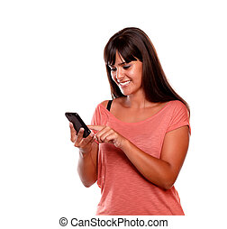 Charming young woman reading message on mobile phone on...