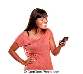 Young woman laughing while reading a message on her mobile...