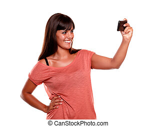 Smiling woman taking a picture with her mobile