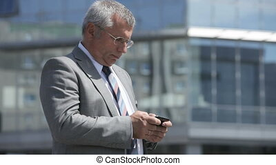Urban message - Tilt up of a busy senior businessman texting...
