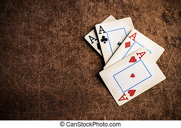 old playing cards on a brown textured background