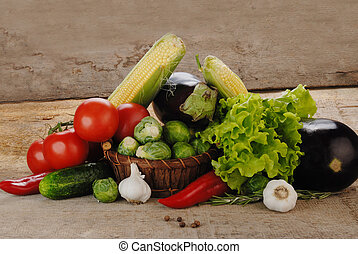 Composition with vegetables in wicker basket on wooden board...