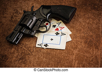 black revolver and old playing cards on a brown textured...