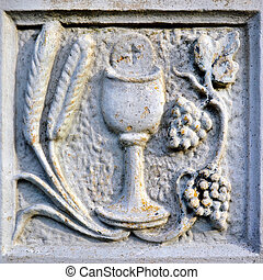 Religion scene with chalice, grain and grapes in stone