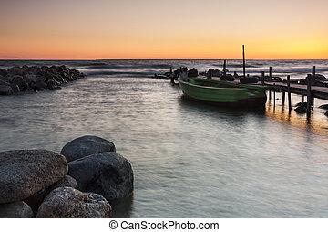 Boat in sea near bridge at sunset