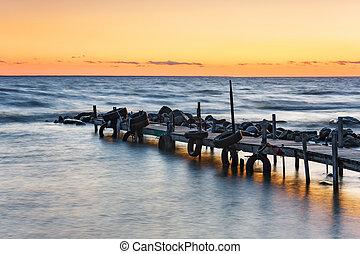 Sunset at sea behind boat bridge