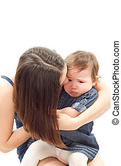 mother soothes a crying baby girl on a white background