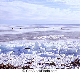 Ice Fishing On Lake Superior - A panoramic scene of ice...