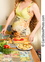 Beautiful pregnant woman with fresh green vegetables on the...