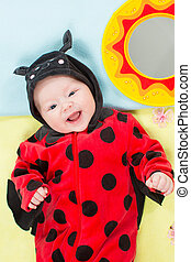 Pretty baby girl, dressed in ladybug costume on green...