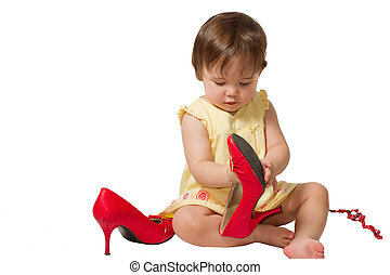 little girl-child trying on mother s big red shoes on a...