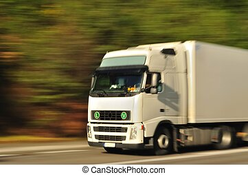 Fast moving white truck, motion blur