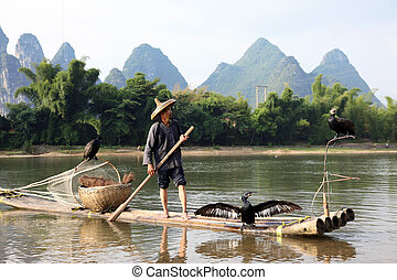 YANGSHUO - JUNE 18: Chinese Chinese man fishing with...
